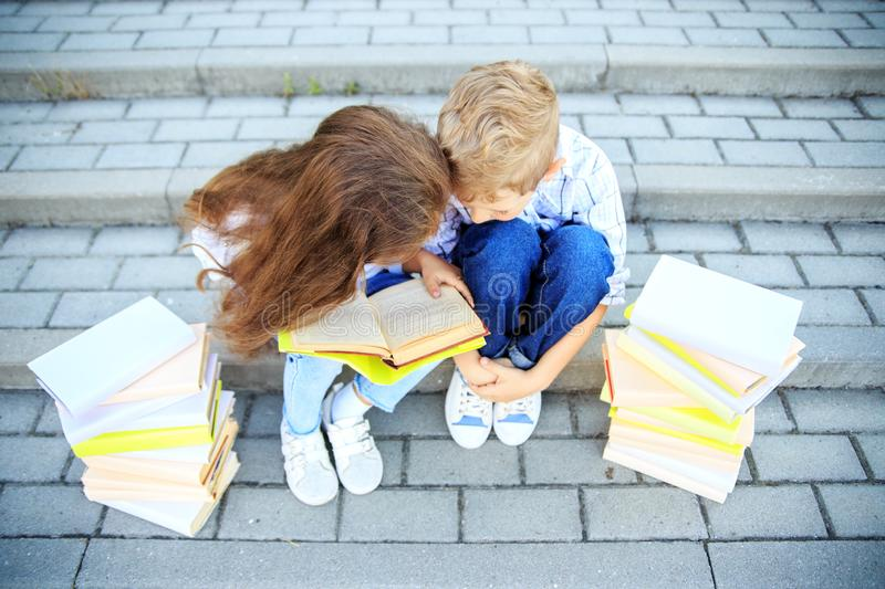 Little boy and girl are studying a book. The concept is back to school, education, reading, friendship and family stock image