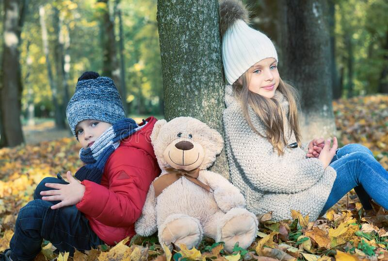 Little boy and girl with Teddy Bear friend sitting on the ground in the autumn park on sunset, nice back light. Little boy and girl with Teddy Bear friend royalty free stock photo