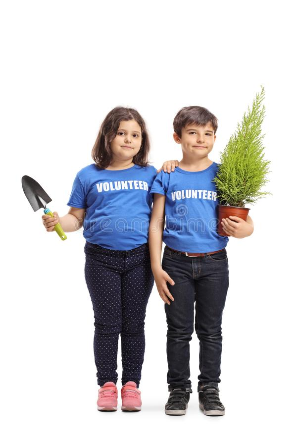 Little boy and girl volunteers holding a plant and a spade royalty free stock photos