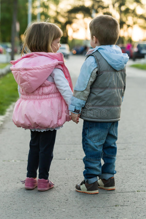 Little boy and girl walking together stock images