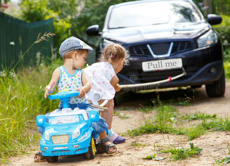 Little boy and girl want to drag real car stock image