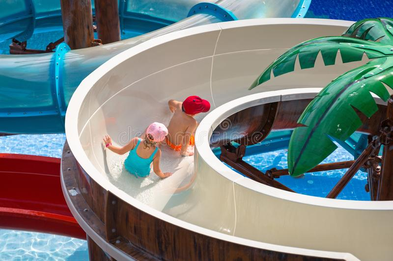 Little boy and girl at the water slide on sun holidays stock image