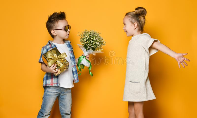 Happy caucasian people boy gives a flowers to his girlfriend isolated over yellow background. stock photo