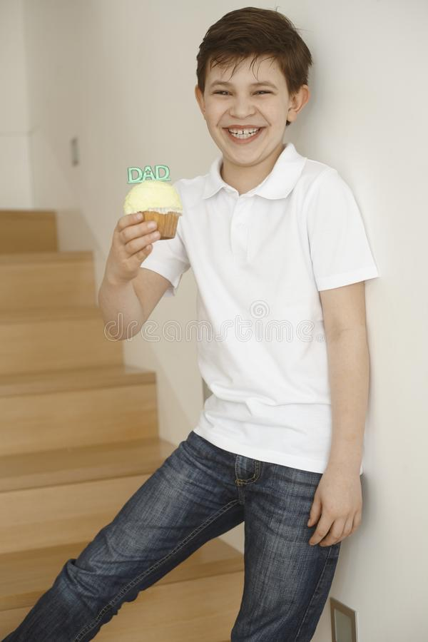 Little boy gives cookie to dad. Little boy standing on stairs giving gift cookie to dad, happy big smile stock photo