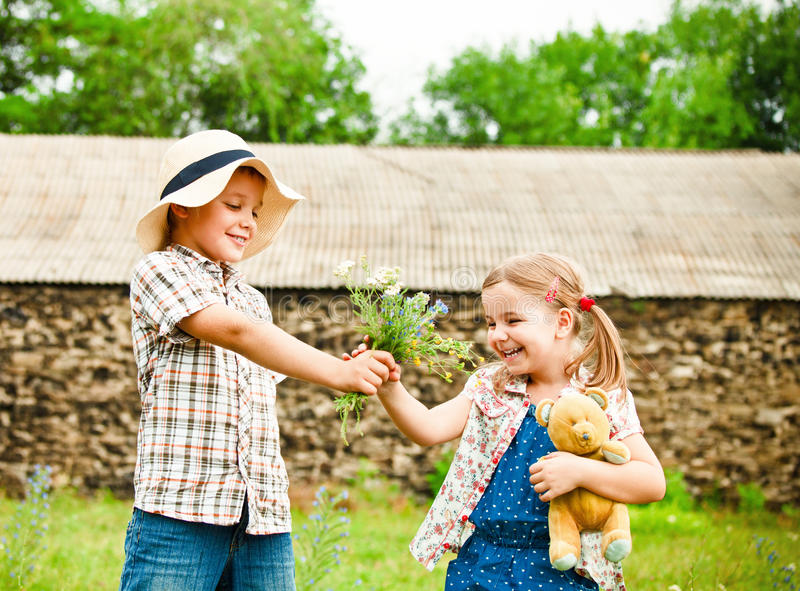 Download Little Boy Gives Flowers To The Little Girl Stock Photo - Image: 28534502