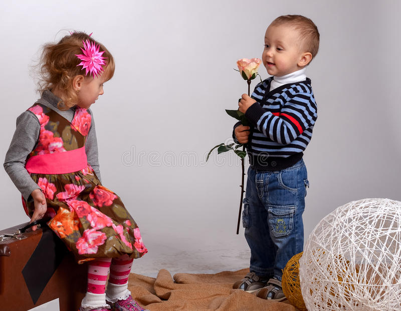 Little boy gives a girl a rose, isolated on white stock photography