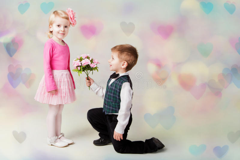 Little boy giving flowers to girl. Hearts bokeh background. st valentine's day present. Romantic gift stock photography
