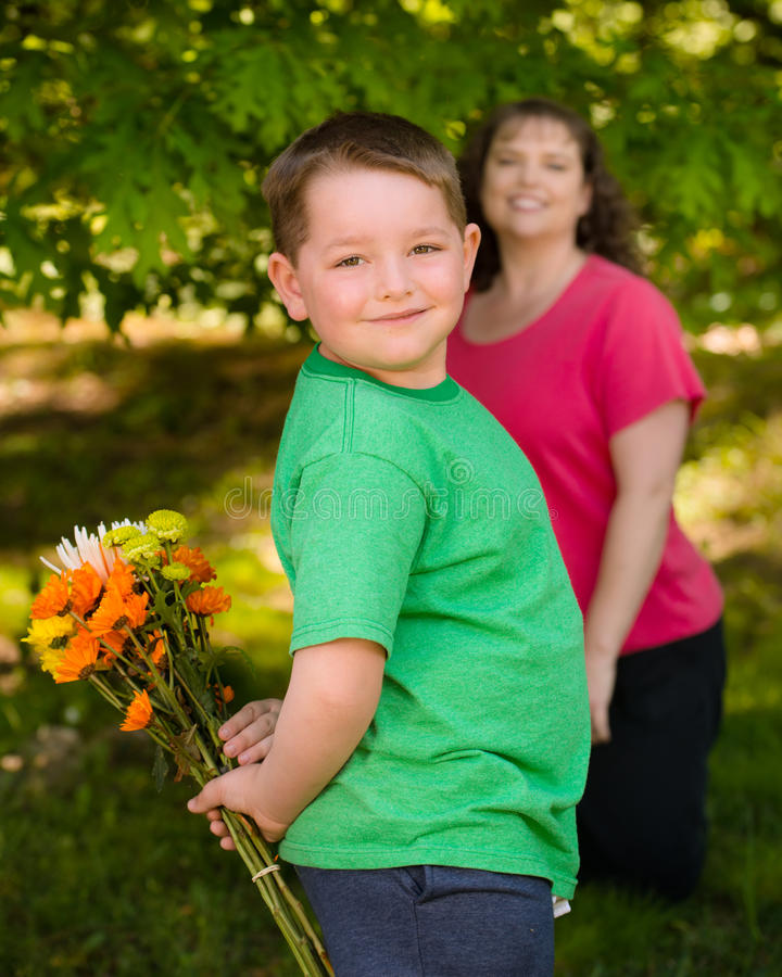 Little boy giving flowers to his mom royalty free stock photos