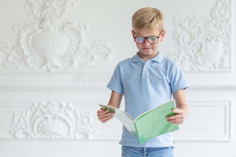 A little boy with glasses and a blue t-shirt is reading a book in a green cover with interest stock image