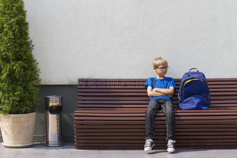 Little boy with glasses sitting on the bench and waiting. Outdoors stock image