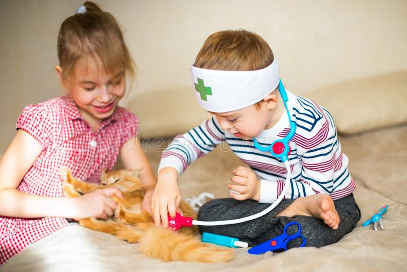 little boy in the glasses with syndrome dawn and blonde girl play with toys and ginger cat royalty free stock photography