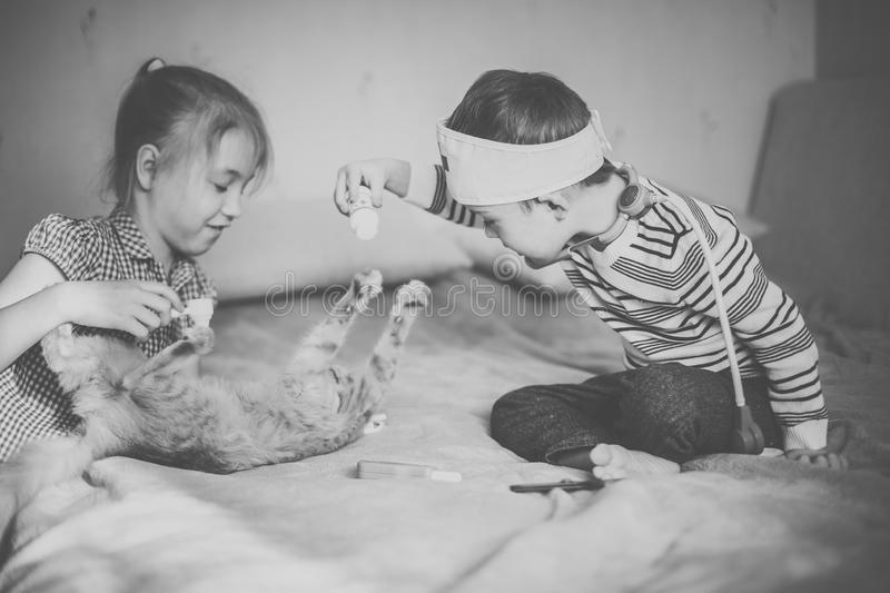 Little boy in the glasses with syndrome dawn and blonde girl play with toys and ginger cat. Black and white royalty free stock image