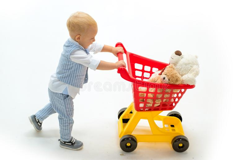 Little boy go shopping with full cart. little boy child in toy shop. shopping for children. happy childhood and care. Savings on purchases. Excitement stock photography