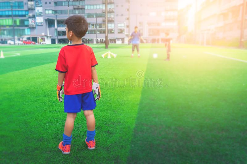 Little boy with goalie gloves standing on a training field stock photography