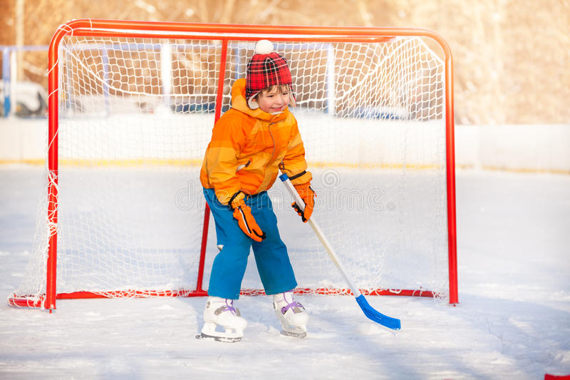 Little boy goalkeeper play ice hockey. Little goalkeeper boy standing in gates holding hockey stick playing ice hockey stock images
