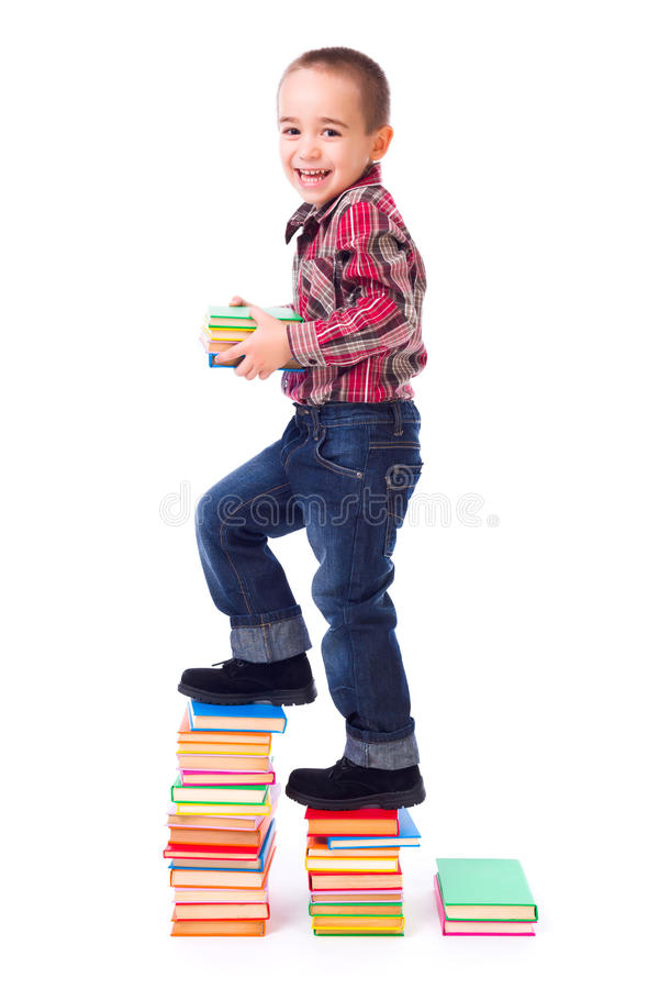 Little boy going up stairs made of books stock image