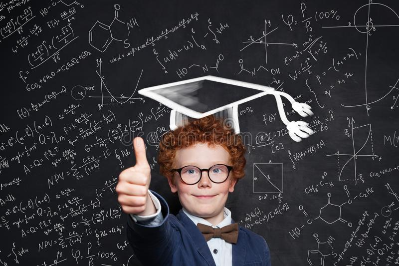 Little boy in graduation hat and glasses. Smart child on science background royalty free stock photography