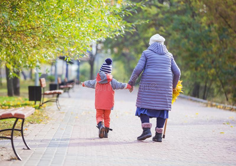 Little boy and great grandmother walking in autumn park stock photo
