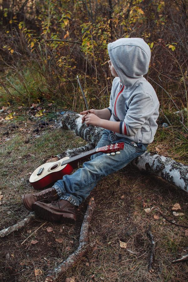 A little boy with a guitar sitting in the Park on a log. Looking away.Talented child stock photography