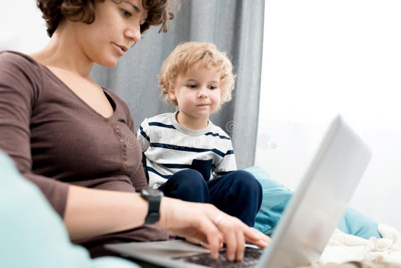 Little Boy hållande ögonen på mamma som använder bärbara datorn royaltyfri foto