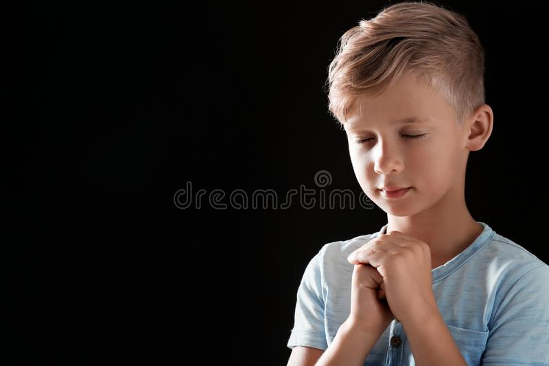 Little boy with hands clasped together for prayer on black background. Space for text royalty free stock photography