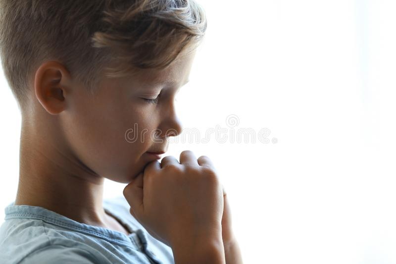 Little boy with hands clasped together for prayer on light background. Space for text royalty free stock image