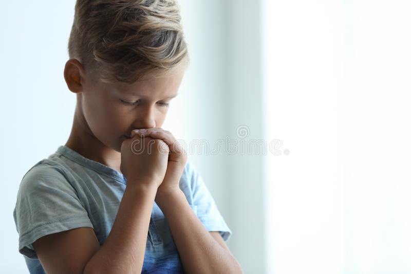 Little boy with hands clasped together for prayer. On light background. Space for text royalty free stock images