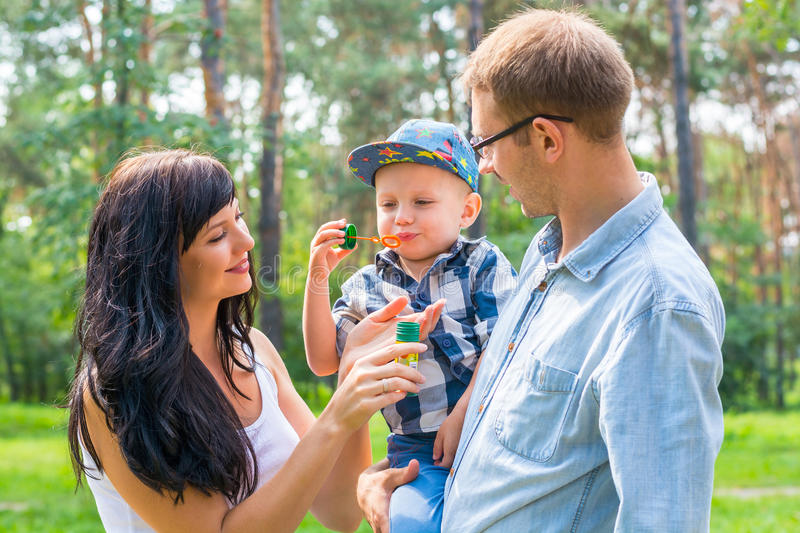 A little boy in the hands of the dad and blow soap bubbles. Mom. Stands by and smiles. Family resting in the park stock photo