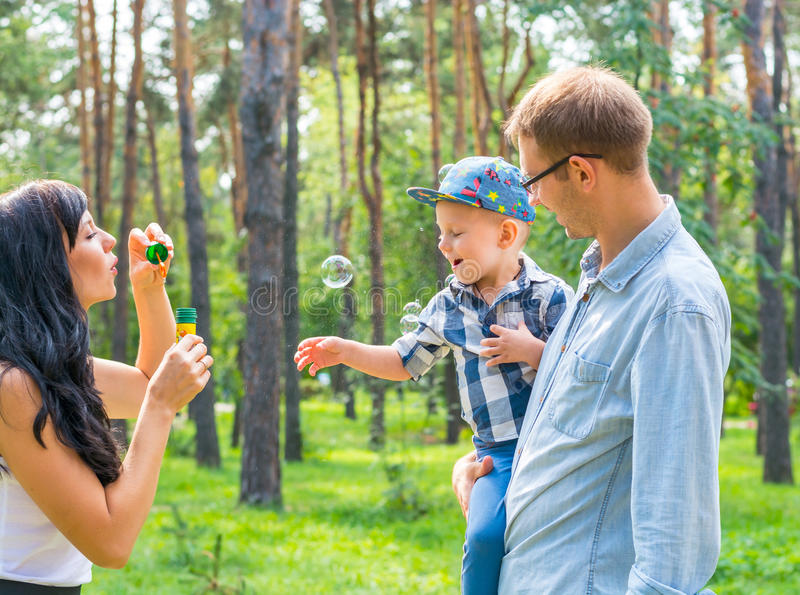 A little boy in the hands of the dad and and his mom blowing soap bubbles. Family resting in the park royalty free stock photo