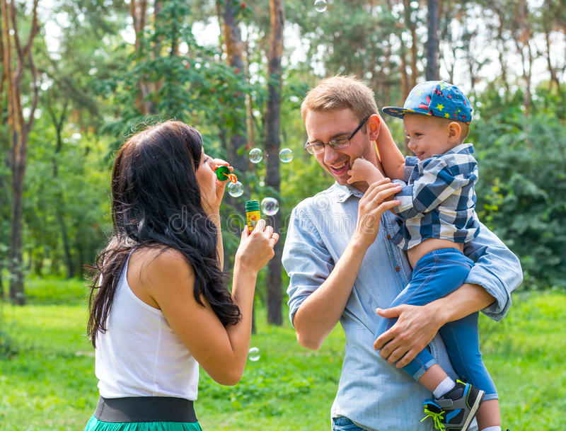 A little boy in the hands of the dad and and his mom blowing soap bubbles. Family resting in the park royalty free stock photography