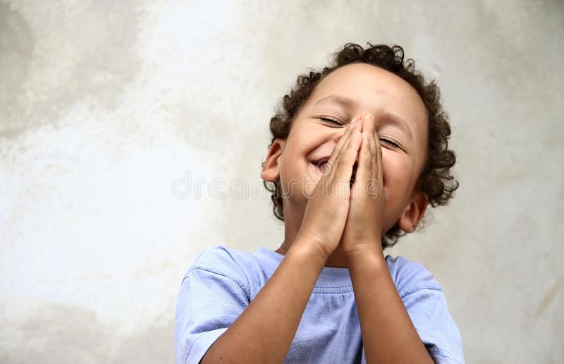 Little boy with hands together praying. Little boy praying to god holding his hands together stock photo