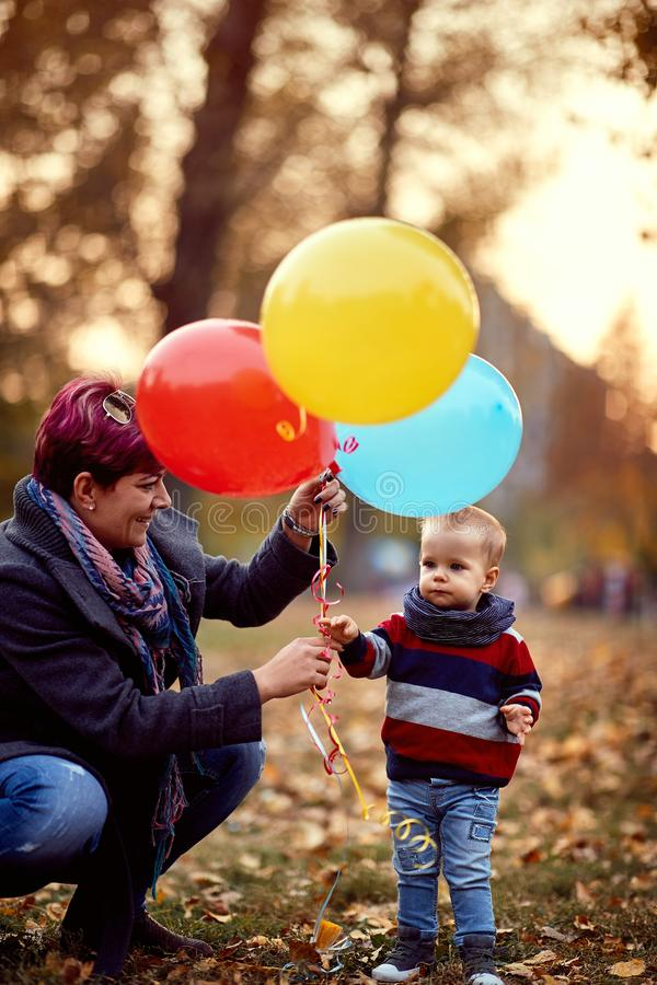 Little boy. Happy childhood. child boy with a bunch of balloons in their hands in yellow autumn park. Family royalty free stock photos