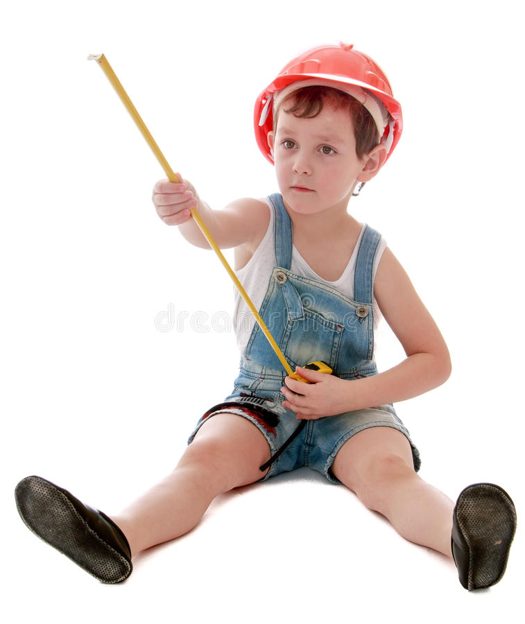 Little boy in a hard hat sitting on the floor royalty free stock photo