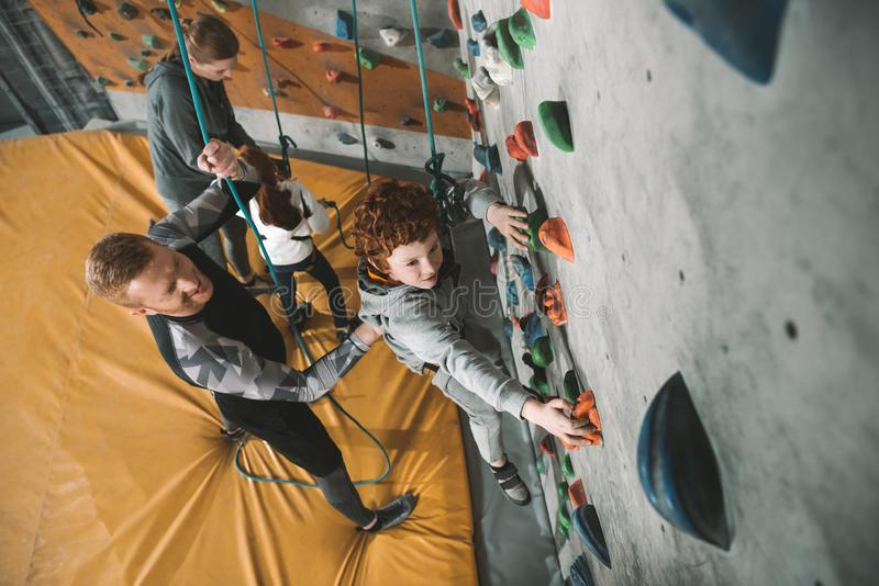 Little boy in a harness climbing a wall at gym with his father securing him from. The back stock image