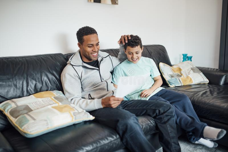 Giving Dad a Homemade Father`s Day Card. Little boy has given his father a homemade card for Father`s Day. They are relaxing on the sofa looking at it together royalty free stock photos