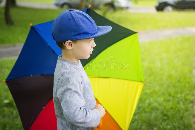Little boy in hat with multicolor umbrella in park after rain on sunny summer day stock photo