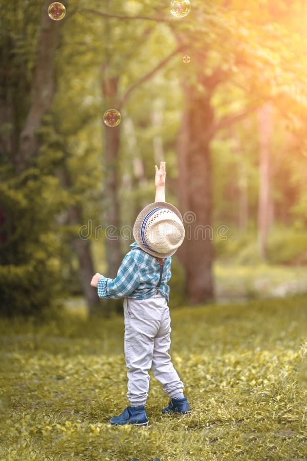 A little boy in a hat reaches for soap bubbles royalty free stock photo