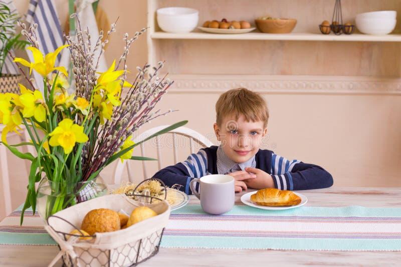 Little boy having breakfast in the modern kitchen. stock image
