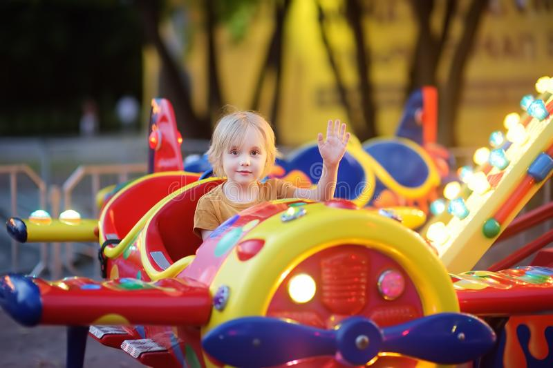 Little boy having fun on attraction in public park. Child riding on a merry go round at summer evening. Attraction, planes, cars,. Illumination, fun royalty free stock photos