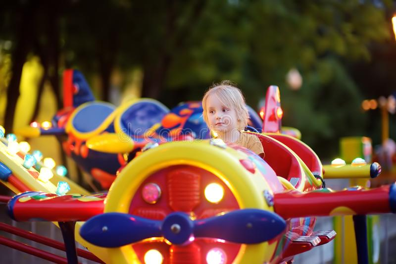 Little boy having fun on attraction in public park. Child riding on a merry go round at summer evening. Attraction, planes, cars,. Illumination, fun royalty free stock images