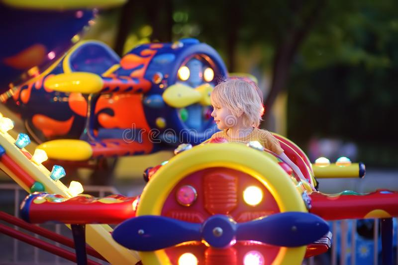 Little boy having fun on attraction in public park. Child riding on a merry go round at summer evening. Attraction, planes, cars,. Illumination, fun stock photography
