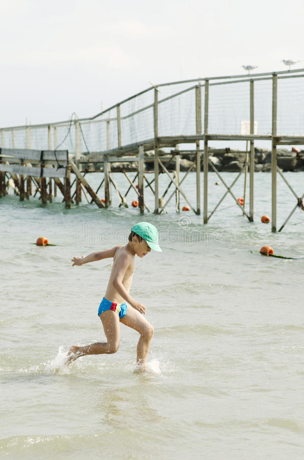 Little boy having fun at beach stock photo