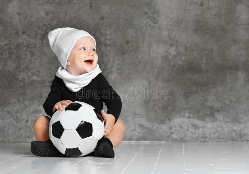 Cute image of baby holding a soccer ball. royalty free stock images