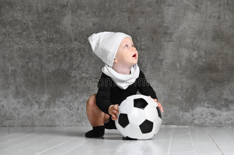 Cute image of baby holding a soccer ball. royalty free stock image