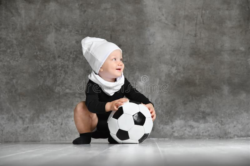 Cute image of baby holding a soccer ball. stock photography