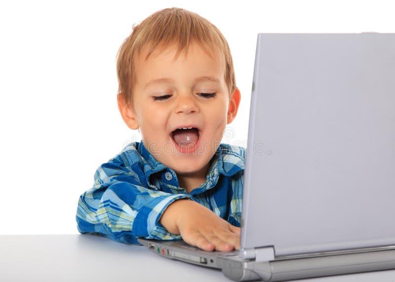 Little boy having fun with laptop stock photos