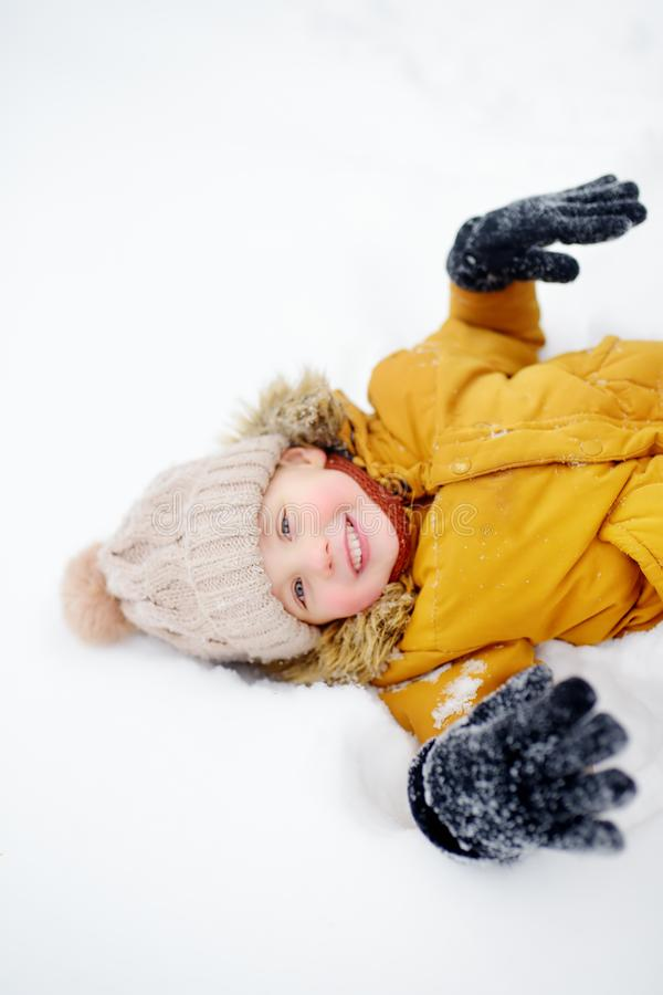 Little boy having fun in the snow. Cute little boy having fun in the snow. Outdoors winter activities for kids royalty free stock images