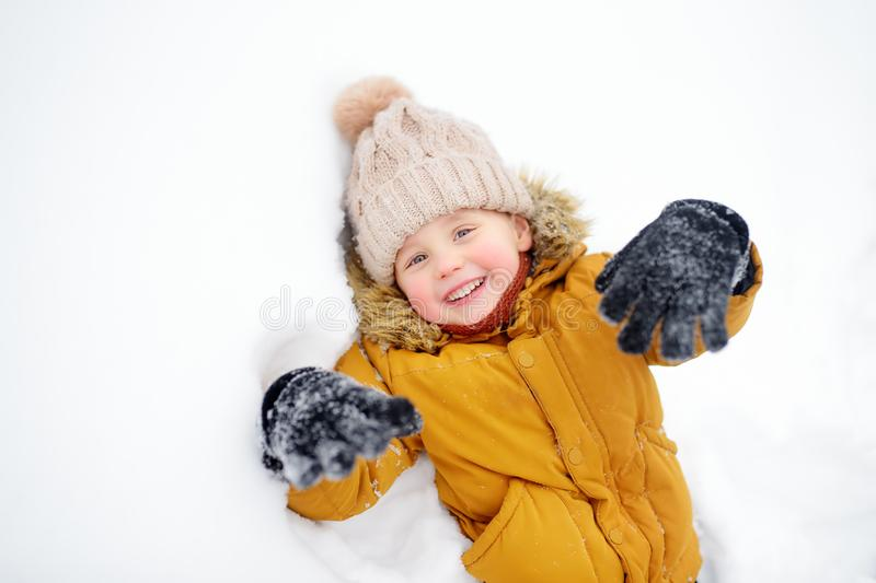 Little boy having fun in the snow. Cute little boy having fun in the snow. Outdoors winter activities for kids royalty free stock photo