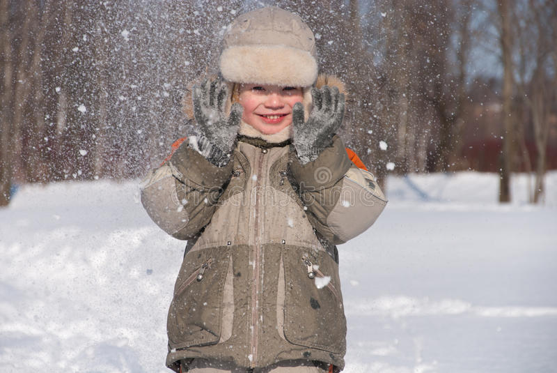 Little boy having fun in the snow royalty free stock photography
