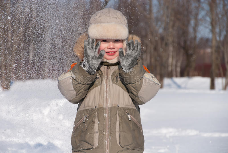 Little boy having fun in the snow royalty free stock photos